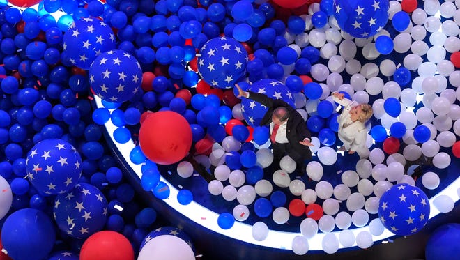 Hillary Clinton and Tim Kaine walk through a sea of balloons at the conclusion of the Democratic National Convention in Philadelphia on July 29, 2016.