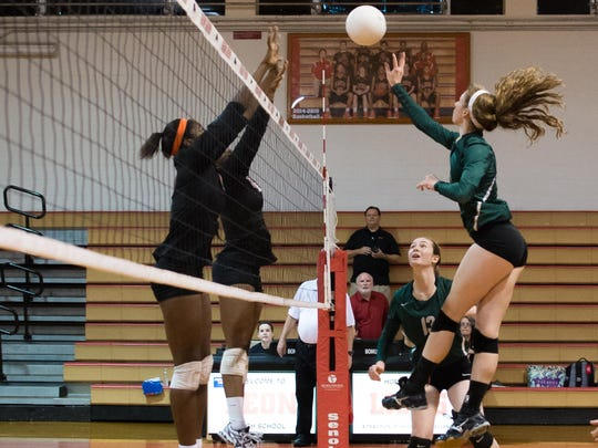 Lincoln's Kaylyn Buchanan tries to tip over the block of Leon sisters Makayla and Daijah Washington. The Lions' blocks were a big reason why Leon won 3-1 and advanced to the regional final.
