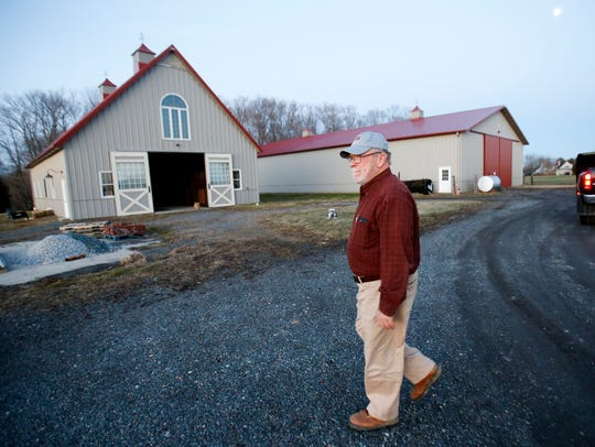 Gary Warren walks past outbuildings on his property
