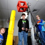 Haslett Robotics Club members Ethan Hunter, Max Doerr and Qian Bates, left to right, fine tune their Minotaurs team robot  as it lifts items for the skyrise challenge as students on the various  teams work on their robots after school at Haslett High School Friday 2/27/2015.