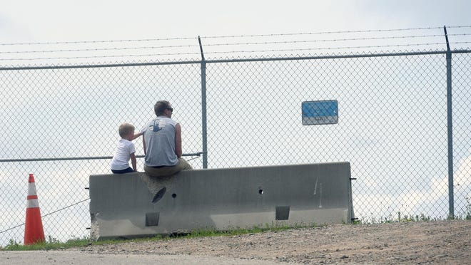 A man and boy sit on a cement barricade at the end of Portsmouth International Airport at Pease where Air Force One and President Donald Trump were supposed to visit July 11. The rally was canceled due to expected storms.