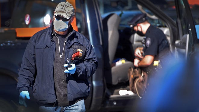 A federal officer holds what is believed to be the handgun belonging to the suspect taken into custody following an alleged gunfire incident Saturday at the Lee Market Basket plaza.