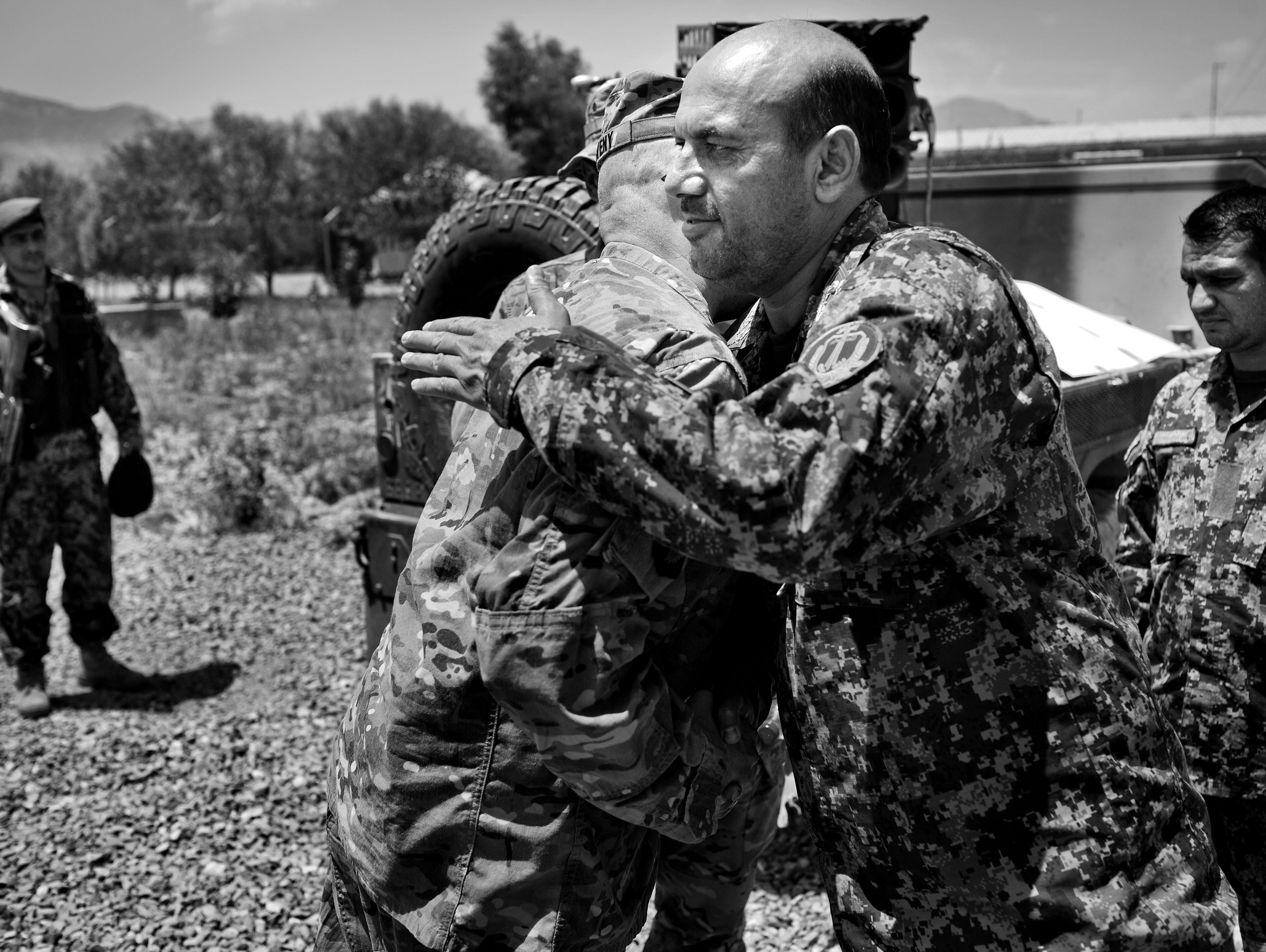 Col. Valery Keaveny, center left, commander of the 4th Brigade of the 101st Airborne Division, hugs General Mohammed Naseer, commander of the 1-203 Brigade, Thunder Corps of the Afghan National Army.