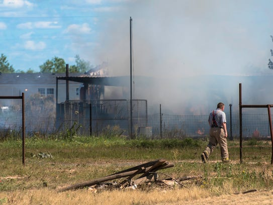 A firefighter looks over the remains of a house destroyed