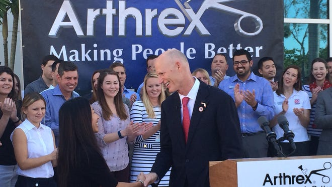 Gov. Rick Scott shakes hands Thursday with Arthrex employee Janet Chow, who was recognized during a press conference in Naples.