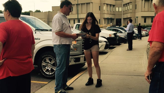 Stop the Funding chairman Bruce Danielson holds a clip board Monday in front of the Minnehaha County Administration Building while Sioux Falls resident Ashley VanGinkel signs a petition to put a planned $25 million city administration building to a public vote.