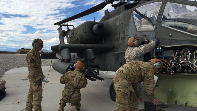 Support soldiers with the 3-6 Cav rearm one of the unit's Apache attack helicopters during aerial gunnery.