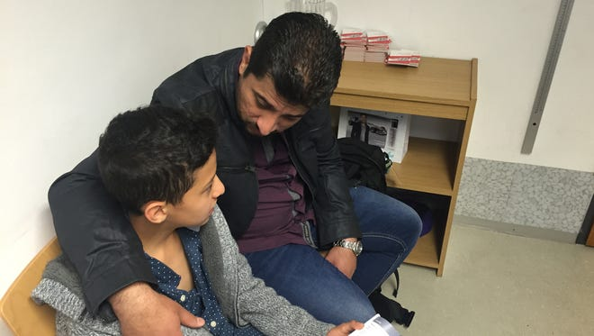 Mohamad Helani, 13, sits with his father Jehad in an immigration office in Dornbirn, Austria, on June 20, 2016.