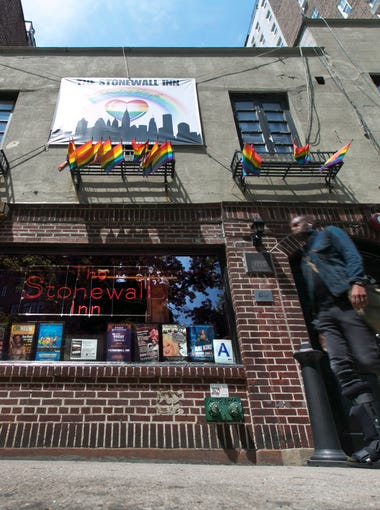 A man passes The Stonewall Inn in New York's Greenwich Village on May 29, 2014. In 2016, President Obama designated the Stonewall Inn and approximately 7.7 acres surrounding it as the first national monument dedicated 'to tell the story of the struggle for LGBT rights.'The gay rights movement broadened - and public awareness grew - after police harassment of patrons at the Stonewall Inn sparked three days of riot on June 28, 1969.