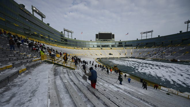 People shovel snow at Lambeau Field on Nov. 29, the day before the Green Bay Packers' game against the New England Patriots.