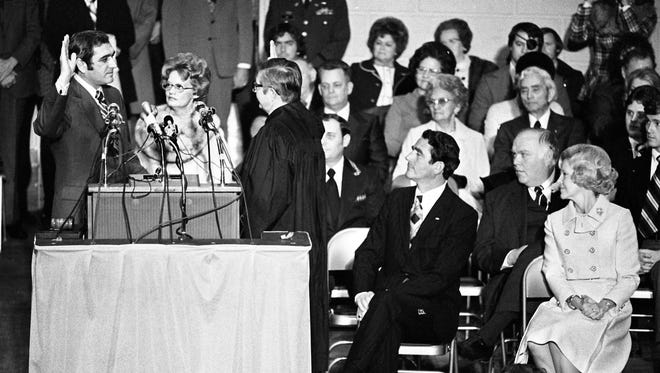 Gov. Ray Blanton, left, repeats the constitutional oath of office administered by State Supreme Court Chief Justice William H.D. Fones, third from left, as his wife, Betty, holds the three Bibles used for the oath-taking during the swearing-in ceremonies inside the War Memorial Audiorium Jan. 18, 1975. Outdoing Gov. Winfield Dunn and his wife, seated at right, watches as power passes.