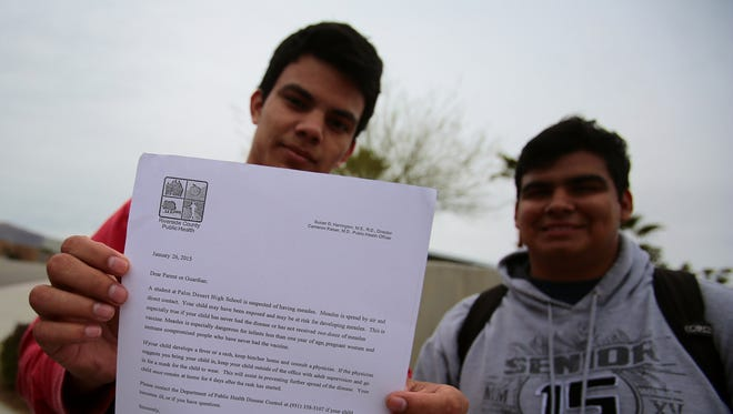 Palm Desert High School students Jesus Vejar, left, and Isaac Perez, both 18, show a letter from the Riverside County Department of Public Health informing them of precautions being taken because of potential measles cases.