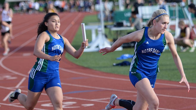 Notre Dame's Halie Ferry, right, stretches for the baton from teammate Melaina Rapisarda in the 800-meter relay in the WIAA Division 1 Track and Field Sectional Meet at Schneider Stadium on Friday.