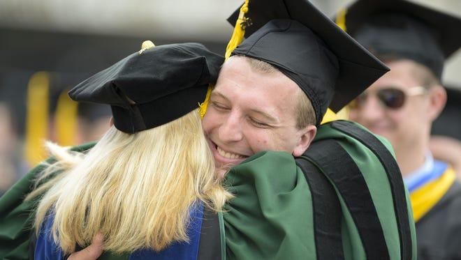Kurt Jansen of Wrightstown hugs one of his professors after Lakeland's graduation ceremony.