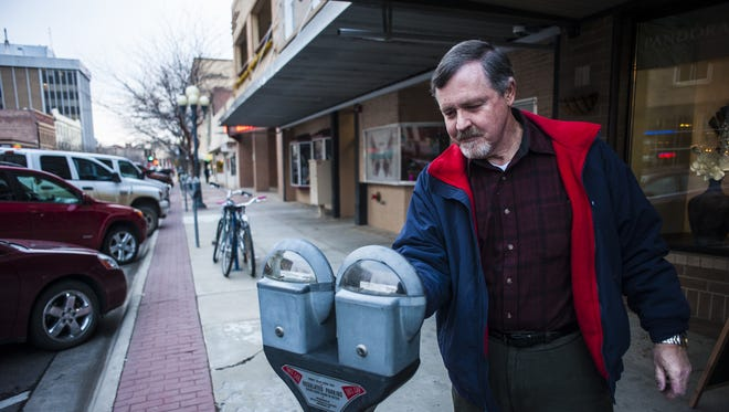 Ron Greene puts coins in a parking meter on Central Avenue in Great Falls recently.