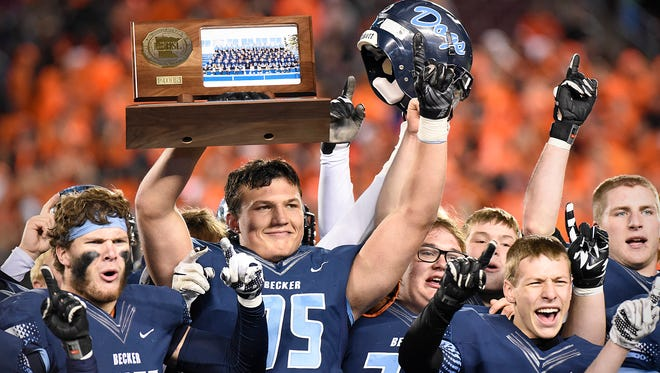 Becker players celebrate with their trophy after beating South St. Paul in the Class 4A state title game Friday, Nov. 13, at TCF Bank Stadium in Minneapolis. Becker beat South St. Paul  35-14.