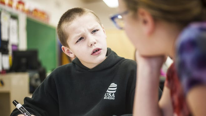 Leo Belgarde, 11, works to understand a math problem as Mira Wyght, 11, helps him in Lincoln Elementary on Wednesday.