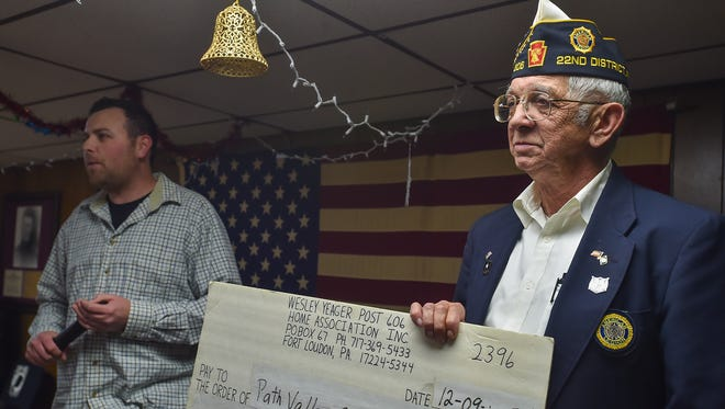 Ray Hawbaker, right, hands a check over to a represenative of Path Valley Outreach inside the Wesley Yeager American Legion Post 606 in Fort Loudon, Pa. on Wednesday, Dec. 9, 2015. Path Valley Outreach recieved $10,000.