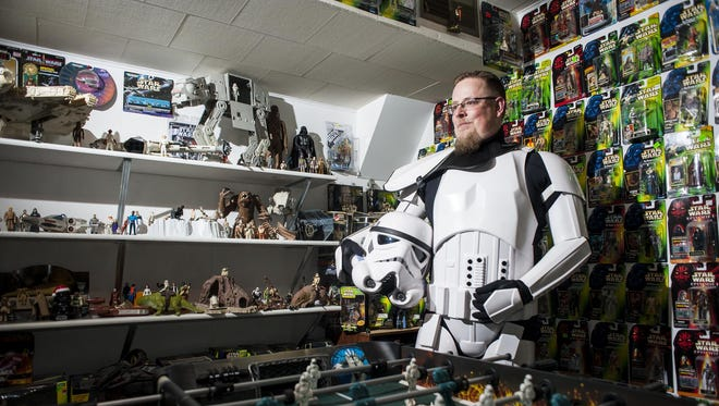 """Pat Douglas stands in a stormtrooper outfit in a basement room filled with """"Star Wars"""" toys Dec. 10. Douglas has been receiving the toys since he was 2 and collecting them since he was 5. Today, he has at least a thousand pieces in and out of packaging."""