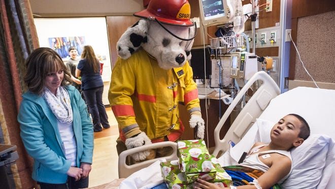 """Tribune writer Andrea Fisher watches while Great Falls Fire Department mascot Sparky delivers toys to Iupati """"Paki"""" Ahping, 6, in Benefis Health System on Thursday."""