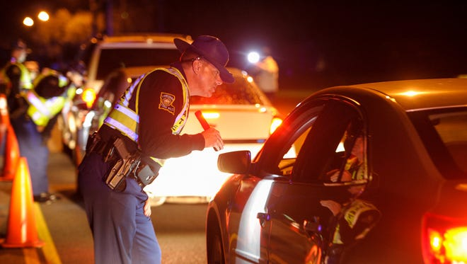 "A Louisiana State Police trooper conducts a sobriety check during a ""no refusal"" DWI checkpoint held Dec. 29."