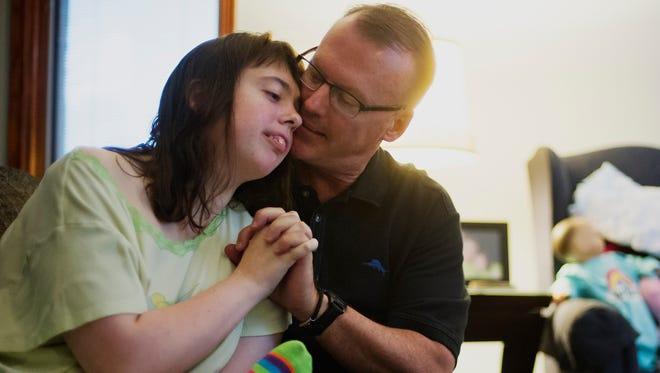 West Des Moines resident Margaret Gaer, 25, was diagnosed with Dravet Syndrome eight years ago but has been fighting the seizes that come with the disease since she was born. She is shown with her father, Steve, on July 10, 2015.