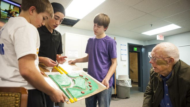 """Lewistown junior high Geographic Information Systems students, left to right, Collin Comes, Sam Fulbright and Ryker Melton show Jack Stone their model of where Big Spring Creek cut through his field in the 2011 flood Wednesday. The students have entered their creek cleanup project in a national Samsung """"Solve for Tomorrow"""" program and are state finalists."""