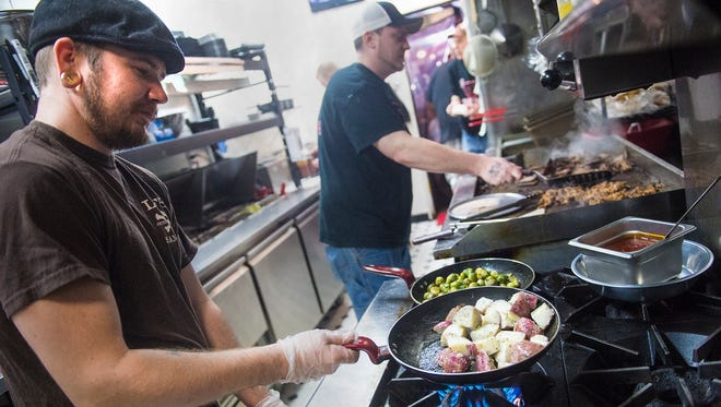 Line cooks Josh Sanders, left, and Kenny DeFelippo prepare food at 3 Hogs BBQ before Super Bowl Sunday on Feb. 7, 2016.