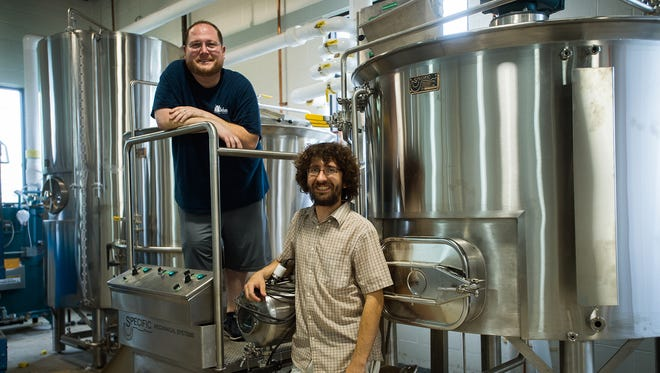 Aldus Brewing President and CEO Jason Mininger, left, and Head Brewer Jeff Groves stand next to a mash tun, a machine that converts starch from barley into sugar.