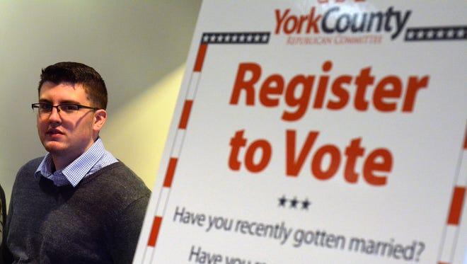 Jacob Taylor of the York College Conservative Forum mans a voter registration booth in the Student Union building during lunch recently. Voter registration has become a partisan issue.