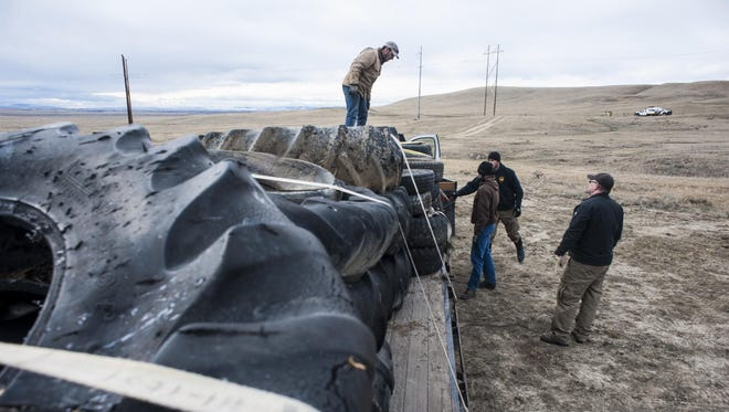 Montana Department of Natural Resources and Conservation employees fasten tires of all sizes found while cleaning a dump site to the back of a truck Tuesday. This dump site is the largest that land manager Andy Burgoyne has witnessed.