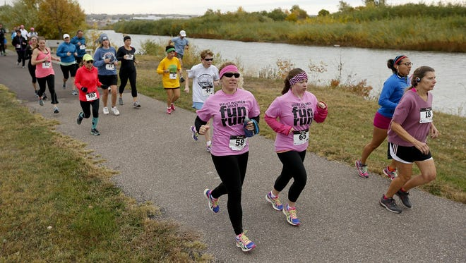 Runners start the 3.5-mile What Women Want Fun Run at West Bank Park on the River's Edge Trial.