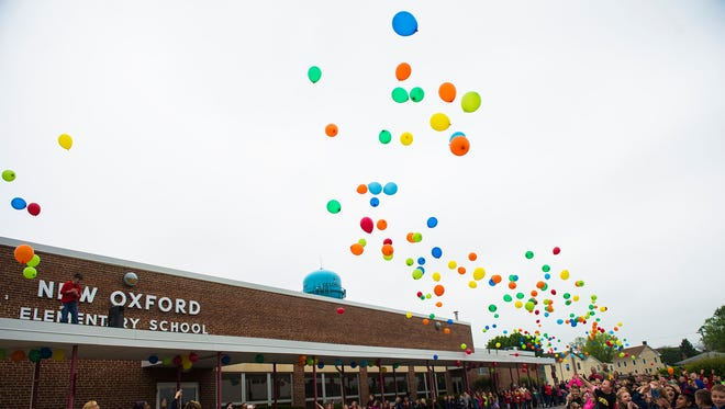 Students release environmentally friendly balloons during the reading parade Wednesday at New Oxford Elementary School.