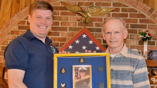 U.S. Air Force Reserve Master Sgt. Eric Sellers, left, and his father, retired U.S. Air Force Master Sgt. Carl Sellers proudly hold the shadow box tribute to Carl's brother, Marlin, who had retired from the U.S. Navy as a senior chief petty officer after 22 years of service.
