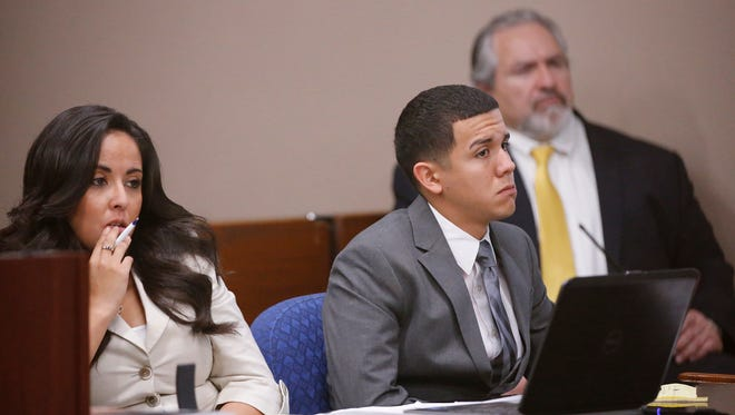 Jan Michael Nieves Delgado sits with one of his attorneys and looks towards the witness giving testimony Friday afternoon during the second day of his trial in the 168th District Court.