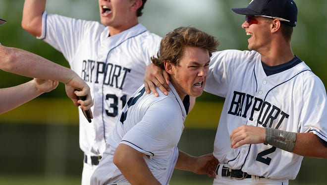Bay Port's Brandon Huettl is mobbed by his teammates after his game-winning hit against Green Bay Preble during Tuesday's FRCC conference game in Suamico.
