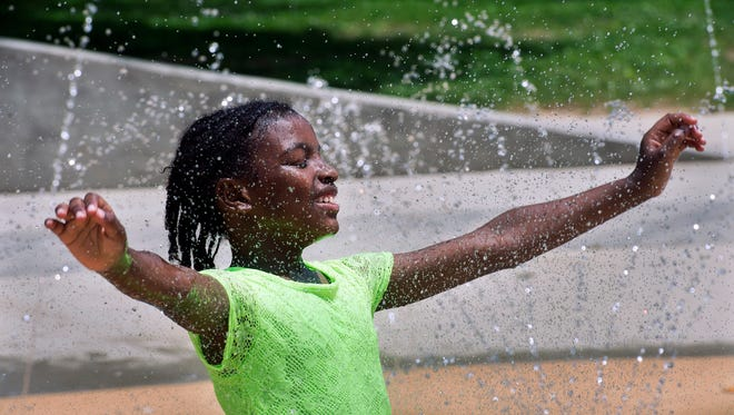 Azyah Walker, 7, of York cools off in Sunday's 80-degree heat at the splash pad in Penn Park in York. The splash pad is set to officially open for the season on June 13.
