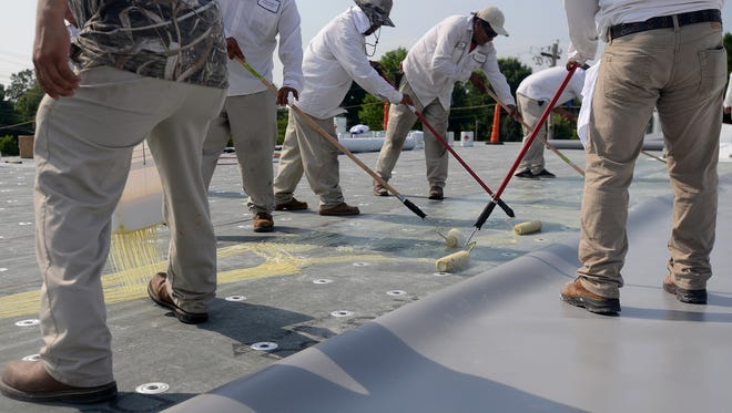 Roofers lay UltraPly TPO on the roof of Pope Elementary School on June 24.