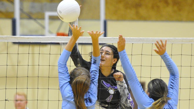 Mission Oak's Samantha Arellano spikes the ball as Redwood's Halle Patterson and Kaylee Tamayo block in a non-league volleyball match at Redwood High School.