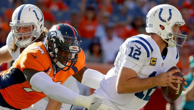 Indianapolis Colts quarterback Andrew Luck (12) is pressured by Denver Broncos outside linebacker DeMarcus Ware (94) but is able to escape during the third quarter at Sports Authority Field at Mile High in Denver on Sunday, September 18, 2016.