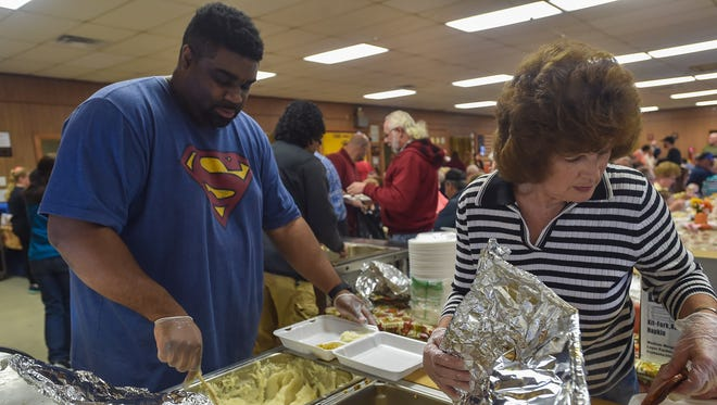 Tyree Sterling, left, and Linda Metcalfe volunteered at the Lemasters Comunnity Center on Thanksgiving Day last year. This year, the Metcalfe family will not be able to have the popular dinner, which attracts well over a thousand people each year, because the community center has been sold and they can't find a new venue that is large enough.