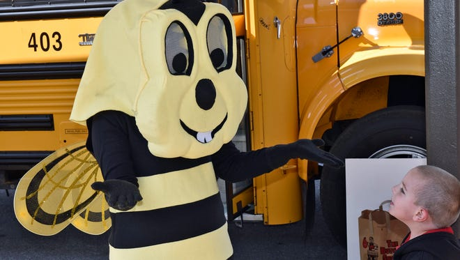 Buzzy the Safety Bee (Lisa Deaven) greets kindergarten student  Christian Hockenberry on Thursday, October 20, 2016 at Stevens Elementary School. CASD Transportation workers conducted a bus safety lesson at the school.