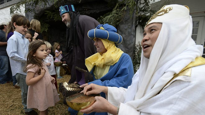 Dress as the three wise men, Justin Gung, right, Phillip Harrison, center, and Tate Rich, top, talks with a group of children during the Walk Thru Bethlehem reenactment at the Woodmont Christian Church on Sunday, Dec. 13, 2015 in Nashville, Tenn.