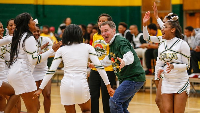 The Crispus Attucks cheerleaders pull Indianapolis Mayor Joe Hogsett onto the court to dance during a community pep rally on Monday, April 3, 2017, in honor of the Attucks' varsity boys basketball team's recent state championship victory.