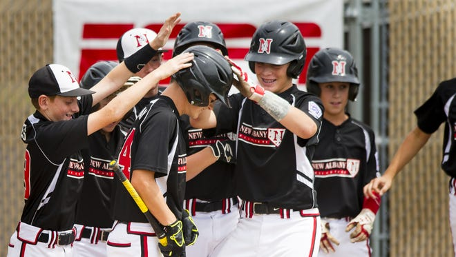 New Albany pitcher Josh Casleman, 11, is greeted at home plate by his teammates after hitting a home run in the bottom of the second inning. New Albany Little League defeated Burlington Little League, of Burlington, Wisconsin, 14-4 in 4 innings, Thursday, August 7, 2014, in the Great Lakes Division advancing to the Championship game on Saturday. The action too place at the Ruben F. Glick Little League Baseball Center on the eastside of Indianapolis.