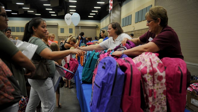 In this file photo, volunteers help parents and their children pick out backpacks during Project Back to School Roundup Saturday, Aug. 12, 2017 in the Ray Clymer Exhibit Hall at the MPEC.