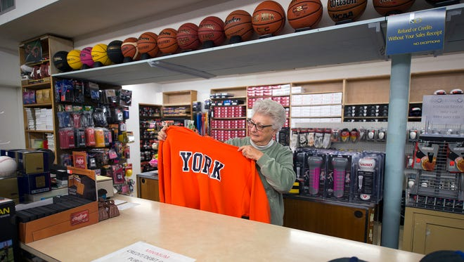 Clare Klinedinst, wife of co-founder George Klinedinst, folds a York sweatshirt with William Penn colors at John M. Grove Sporting Goods in the 700 block of East Market Street in York.