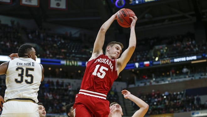 Indiana Hoosiers guard Zach McRoberts (15) pulls down a rebound after a foul shot in overtime against the Notre Dame Fighting Irish during the Crossroads Classic at Bankers Life Fieldhouse in Indianapolis on Saturday, Dec. 16, 2017. McRoberts found forward Juwan Morgan (13) for the dunk and the go-ahead score.