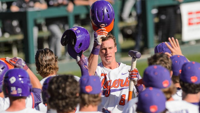 Clemson short stop Logan Davidson (center) celebrates with teammates after hitting a homerun against South Carolina on Sunday in Clemson's Doug Kingsmore Stadium.