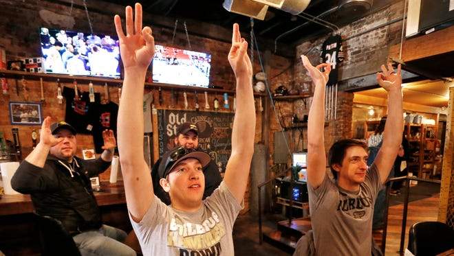 Watching Purdue play Cal State Fullerton in the NCAA basketball tournament at Friday, March 16, 2018, at DT Kirby's, brothers Dakota, left, and Caleb Koontz raise their arms as the Boilermakers put up a three-point shot. Dakota is a junior at Purdue and Caleb works at the university.